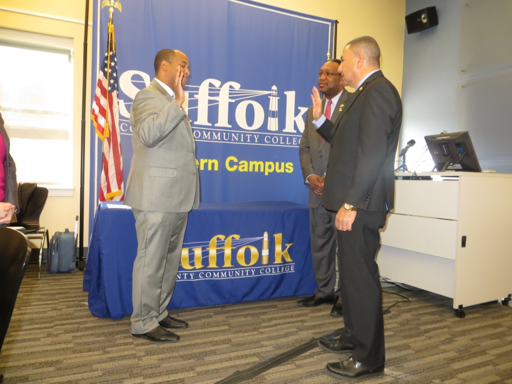 Assemblyman Phil Ramos (right), alongside Dr. Shaun L. McKay, President of SCCC, administers the oath of office to Bergre Escorbores (left) as Trustee of Suffolk County Community College. In addition