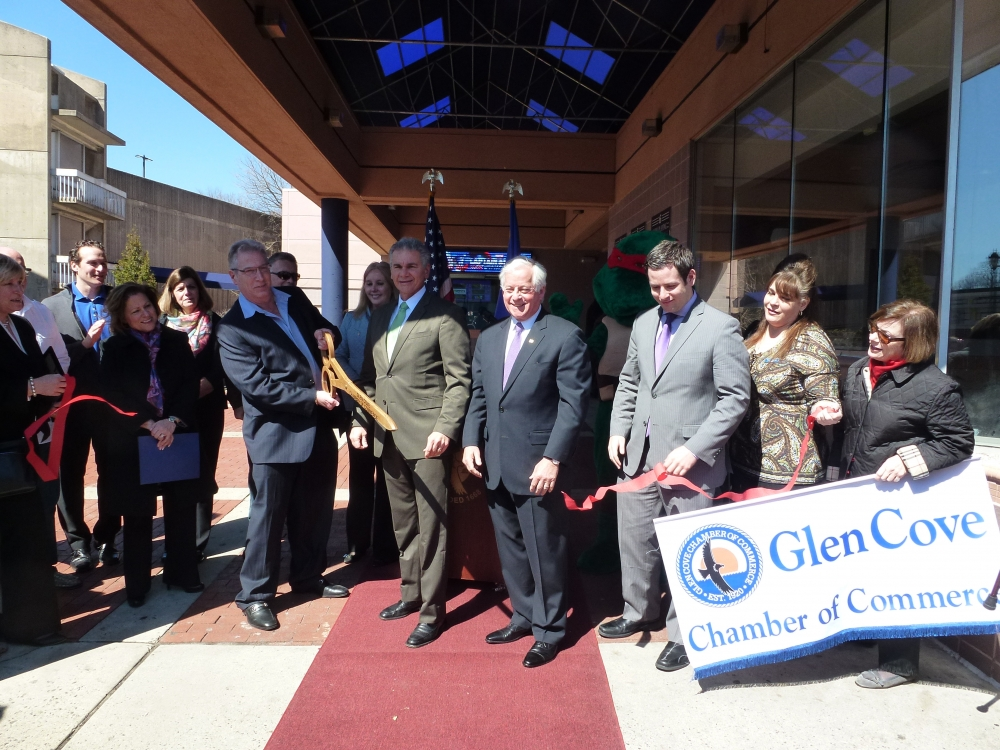 Assemblyman Charles Lavine (D-Glen Cove) center, joins Jay Levinson, left, President of J Jay Theatre Corp in East Meadow and operator of the newly renovated Glen Cove Theater, as he snips the ribbon for the grand opening. Joining the festivities were Glen Cove Mayor Reggie Spinello, members of the Glen Cove Chamber of Commerce and the Business Improvement District. Levinson, who operates movie theaters in Merrick and East Northport, had leased the Glen Cove Theater 15 years ago. When it went into foreclosure last year, the note for the theater was bought by the DiNoto Group. They then brought Levinson back to operate it again. Local restaurant owners say business has been down around 30% since the theater closed. The theater, which has digital projectors and plans to show top movies, will also have a new price structure to be competitive with franchise cinemas.