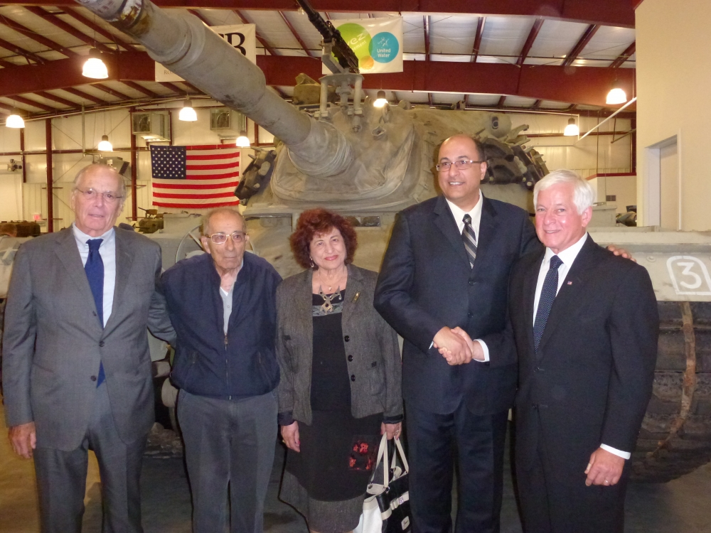 Assemblyman Charles Lavine (D-Glen Cove) right, greets Ido Aharoni, Consul General of Israel and his parents Ahuva and Emanuel Aharoni at an event at the Museum of American Armor at Old Bethpage Villa