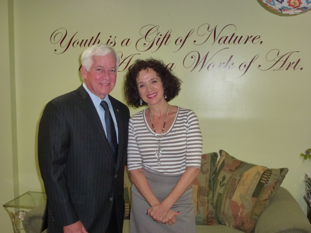 "Assemblyman Charles Lavine (D-Glen Cove) and Lisa Craig, Program Director of the Glen Cove Adult Day Program, stand beneath a sign that states ""Youth is a Gift of Nature, Aging is a Work of Art"" during Assemblyman Lavine's recent visit to the Glen Cove Senior Center to meet and greet the seniors who are benefitting from a $5,000 grant he secured for social and recreational activities as well as general day care."