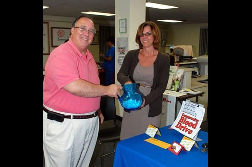 Assemblyman Michael Montesano and Clare Trollo, Hicksville resident and Gold Coast Public Library Adult Program Coordinator, raffle gifts to donors at the Assemblyman's community blood drive on July 23.