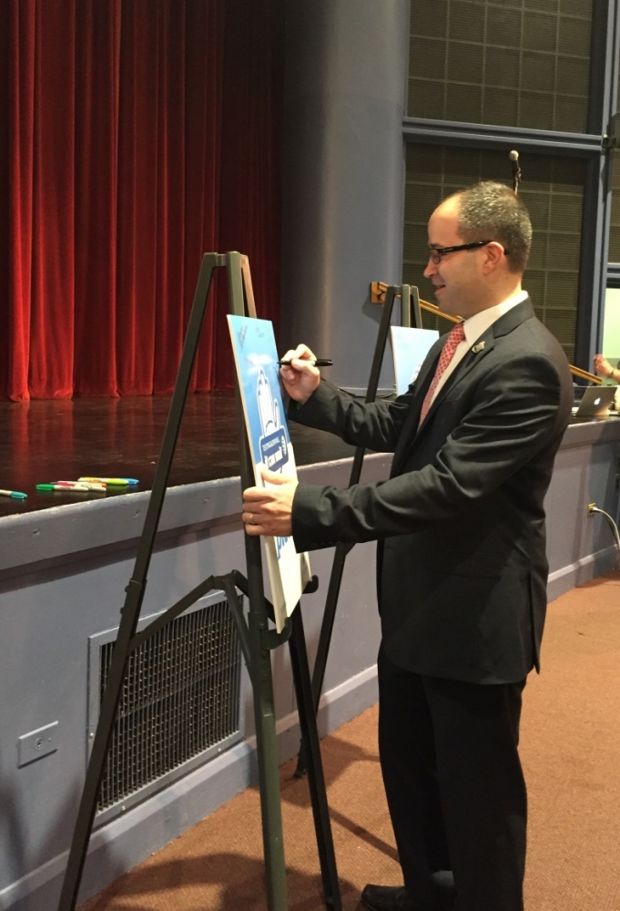 "Assemblyman Ed Ra (R-Franklin Square) signs AT&T's ""It Can Wait"" pledge to avoid distracted driving following his presentation at Garden City High School."