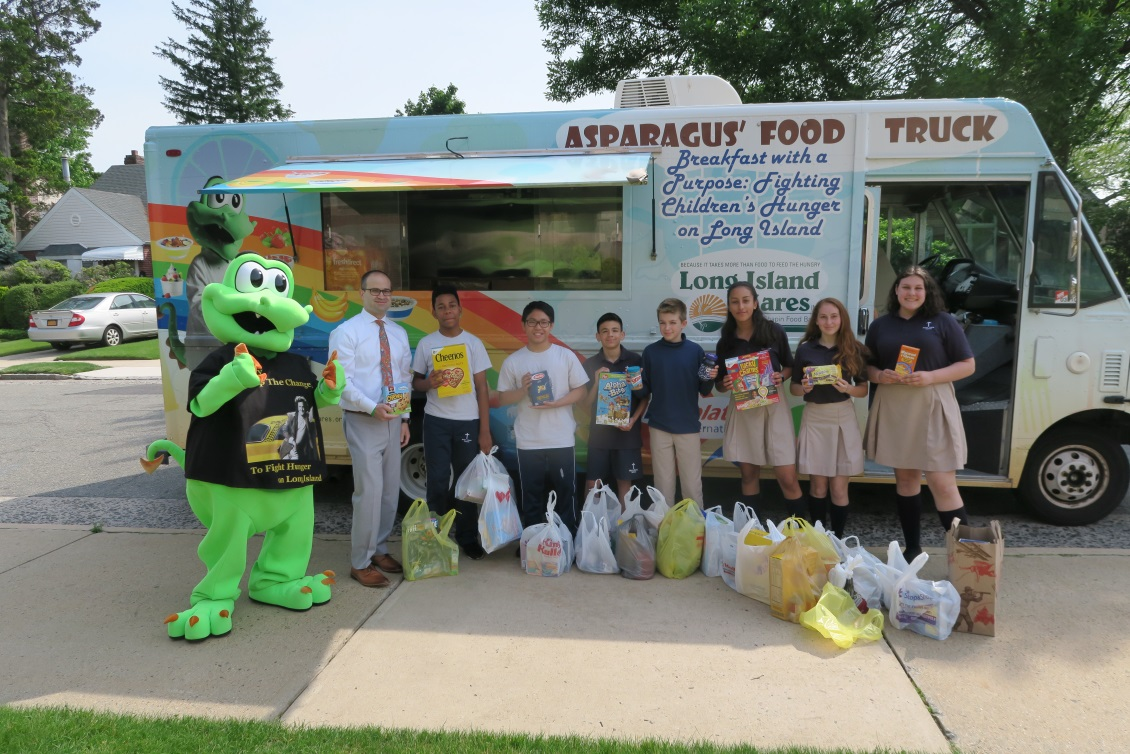 Asparagus the Dragon, mascot of Long Island Cares, picked up the 1,033 pounds of food from Assemblyman Ed Ra (R-Franklin Square) and students at Notre Dame School, New Hyde Park, on Friday, June 8.<br />&nbsp;
