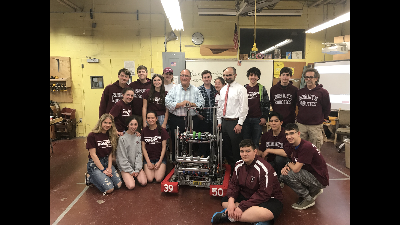 "Assemblyman Montesano, Assemblyman Ra and North Shore High School Robotics Team Supervisor Stephen Peroni pose with team members and their creation, ""Fran""."