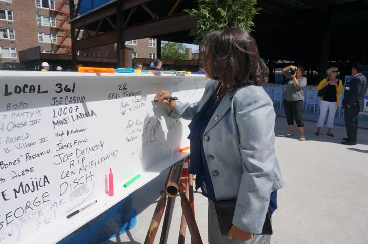 Assemblywoman Solages signs the beam at the Winthrop Research and Academic Center Topping Out ceremony.