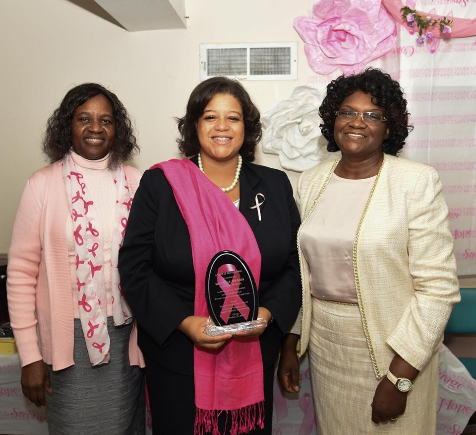 Local advocates and community leaders award Assemblywoman Solages with a plaque acknowledging her commitment to combating breast cancer.