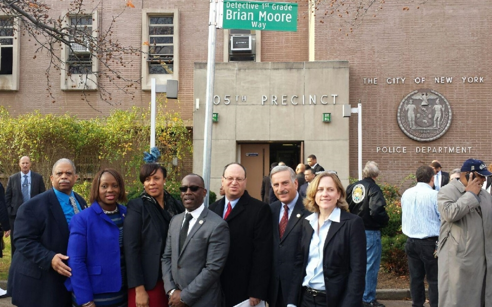 "Senator Leroy Comrie, Councilwoman Vanessa Gibson, Assemblywoman Alicia Hyndman, Councilman I. Daneek Miller, Councilman Barry Grodenchik, Assemblyman David Weprin, & Borough President Melinda Katz join together outside the 105th Precinct in Queens Village following a ceremony to rename the corner of 222nd Street and 92nd Avenue as ""Detective 1st Grade Brian Moore Way"" in honor of NYPD Police Officer Brian Moore."