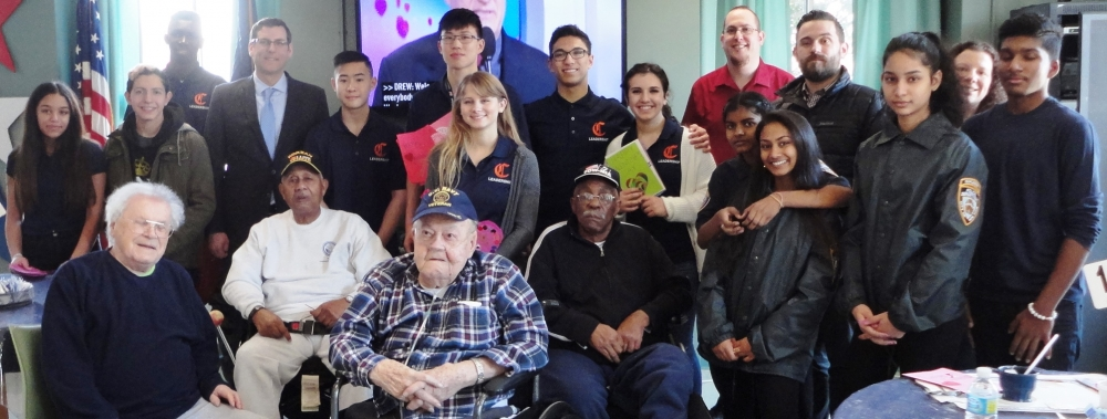 Assemblyman Edward C. Braunstein is pictured with veterans at the St. Albans Community Living Center, along with his staff and Benjamin N. Cardozo High School students and faculty.
