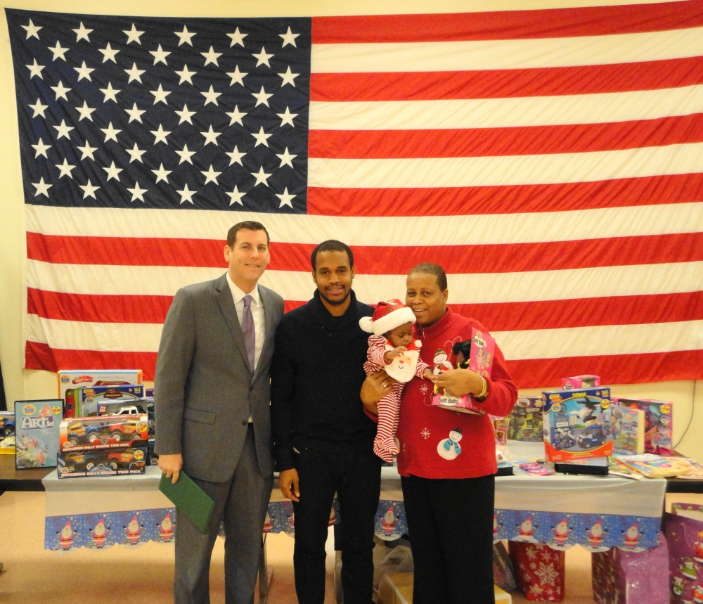 Assemblyman Braunstein is pictured at Fort Totten with a military family which received donations from his office's 6th Annual Toy Drive.