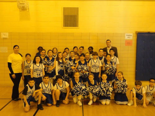 Assemblyman Braunstein and Principal Vanessa Rosa with the student participants and the cheerleading squad from PS 169. The students celebrated after their big victory in the School Spirit Week Staff vs. Student Basketball Game.