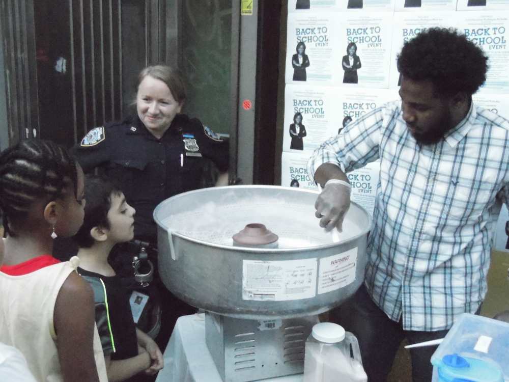 Director of Constituent Support Services, Francois Jeanty, serves cotton candy to residents of the 42nd Assembly, during the Back-to-School Supply Drive.
