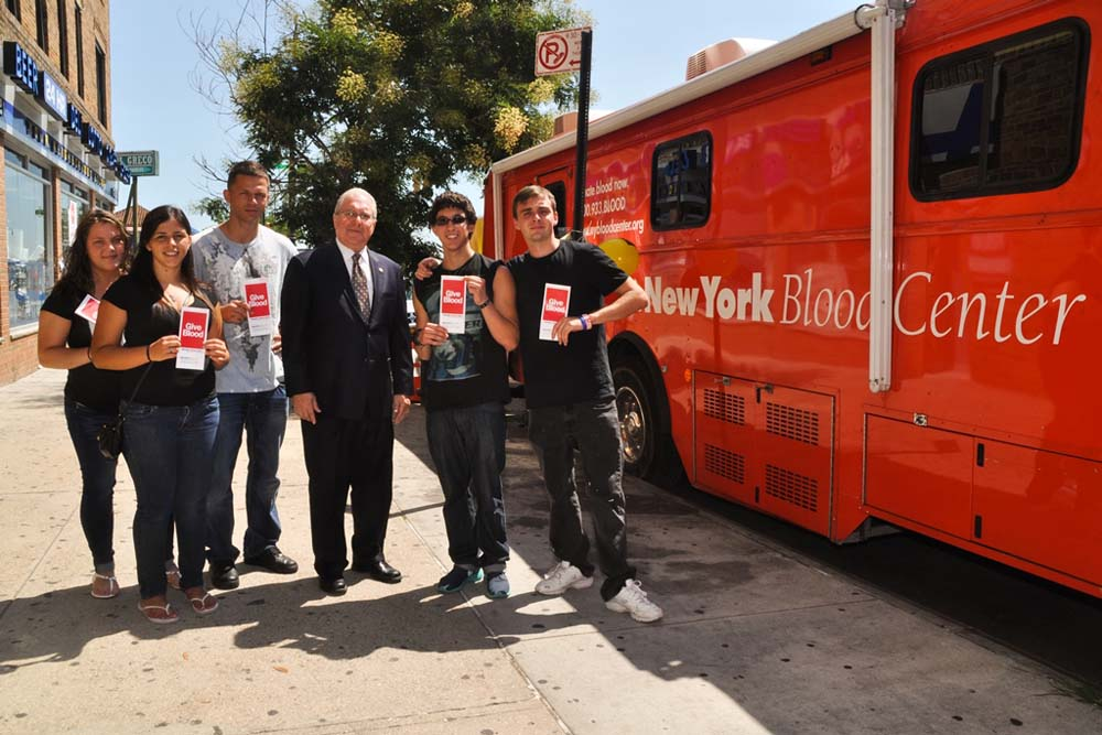 Assemblyman Steven Cymbrowitz with students from Dynamic Youth in front of the New York Blood Center's Bloodmobile during his annual Community Blood Drive.