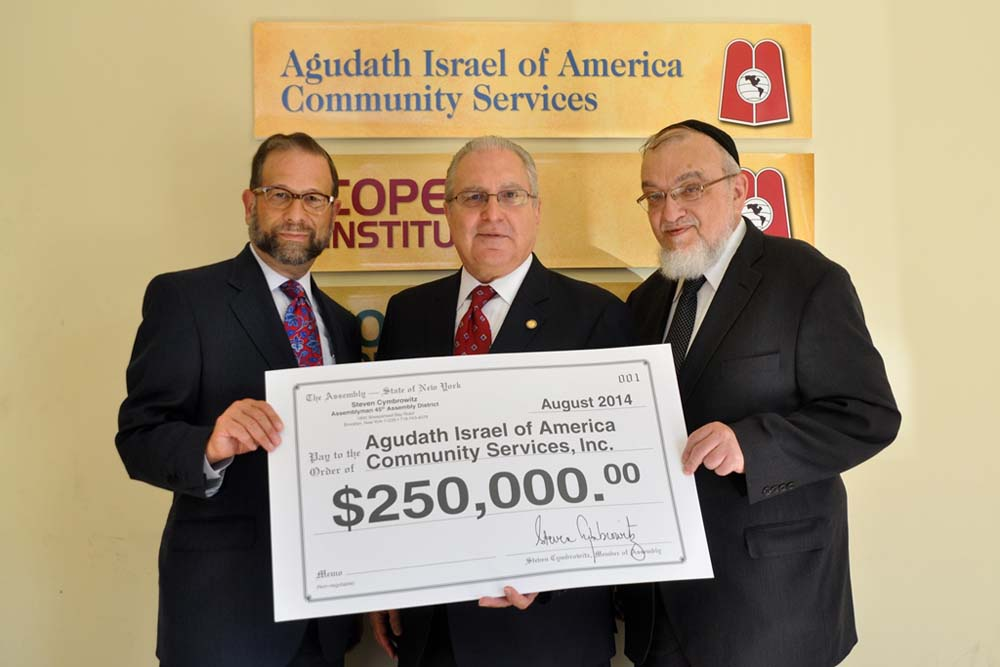 Assemblyman Steven Cymbrowitz presented an oversized check for $250,000 this week to Leon Goldenberg (left) and Rabbi Shmuel Lefkowitz of Agudath Israel of America for the expansion of space for Aguda