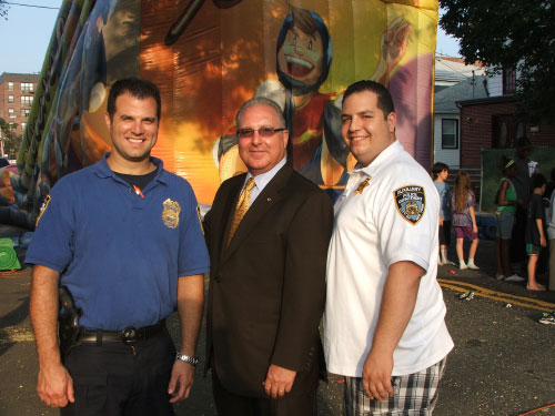 "Assemblyman Cymbrowitz joined hundreds of community residents who attended the 61st Precinct's ""National Night Out."" The annual event is designed to bring the community together with police officers in an unstressful, upbeat setting. Pictured, with the Assemblyman, in front of one of the inflatable children's rides (L-R) are Lt. Michael Doyle and Auxiliary Police Lieutenant Steven Matsas. Assemblyman Cymbrowitz joined his staff answering questions, providing informational pamphlets and offering free give-a-ways at a table they had set up."