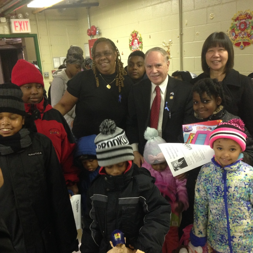 Assemblymember William Colton, Community Relations Director Nancy Tong with Marlboro Housing Residents Association President Betty James at a toy giveaway at Marlboro Housing.