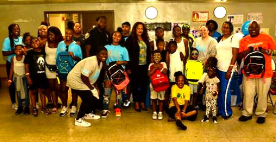 Celebrating the Glenwood Housing Development Annual Back Pack Giveaway where over 220 children received backpacks.