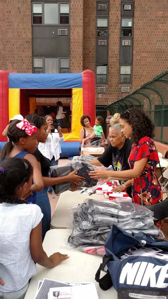 Assemblywoman Latoya Joyner offers books and school supplies to children at River Park Towers.