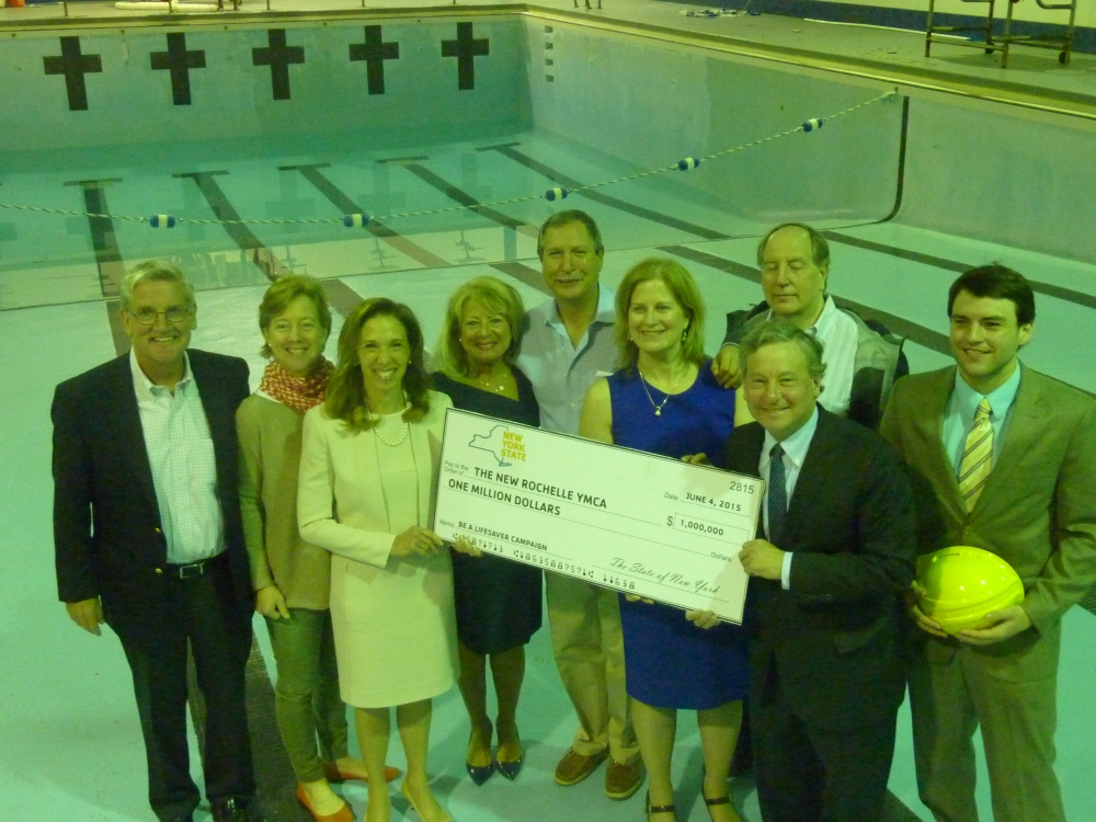 Assemblywoman Amy Paulin and Assemblyman Steve Otis in the pool with the New Rochelle YMCA Board of Directors presenting them with a check to help rebuild the pool.
