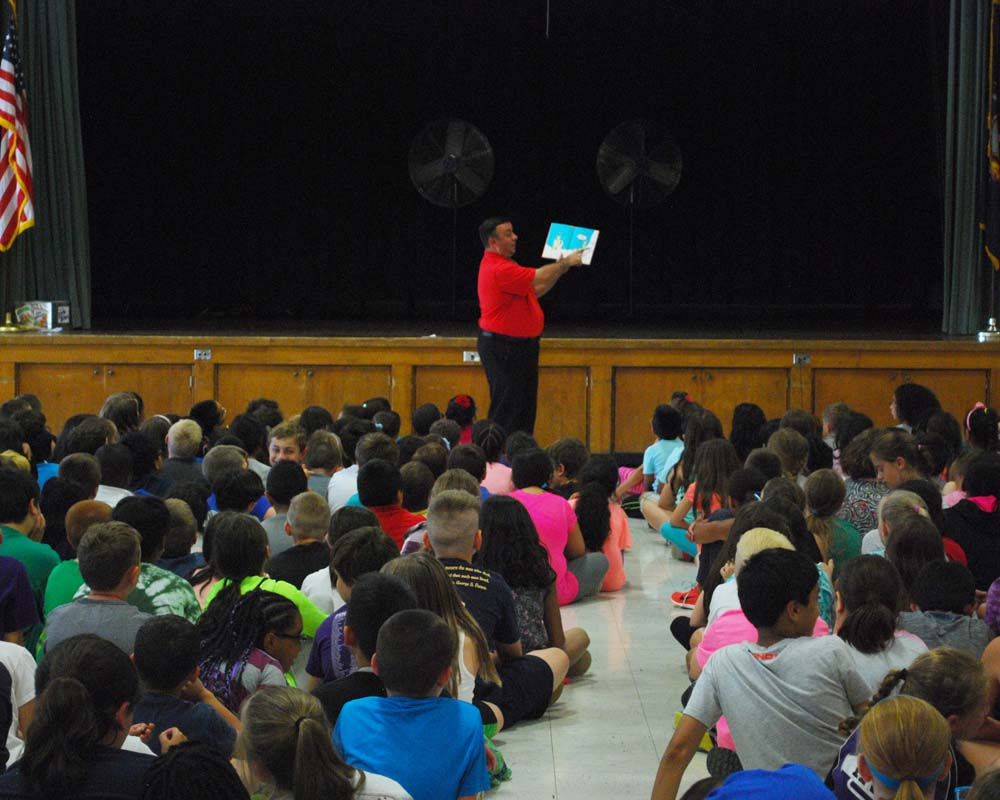 "Assemblyman Karl Brabenec (R,C,I-Deerpark) reads ""Green Eggs and Ham"" to a crowd of several hundred students at Pine Tree Elementary School in Monroe Monday, encouraging them to participate in the Assembly's Summer Reading Challenge"