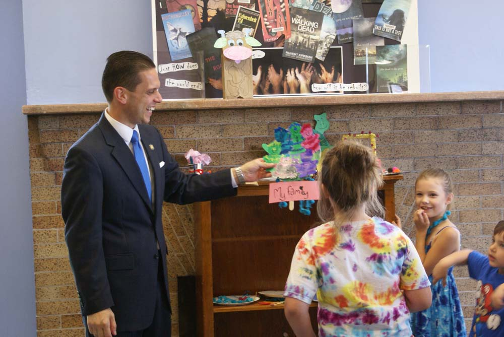 Assemblyman Santabarbara views Children's Art Projects entries at the Amsterdam Free Library.
