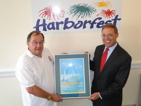 Doug Buske, Executive Director of Harborfest, left, presented Assemblyman Will Barclay (R,C,I—Pulaski) with a framed print of the official Harborfest poster and brochure cover.  The winning design was created by G. Ray Bodley student Chlarissia Crast. Harborfest will take place July 23-26 in Oswego.