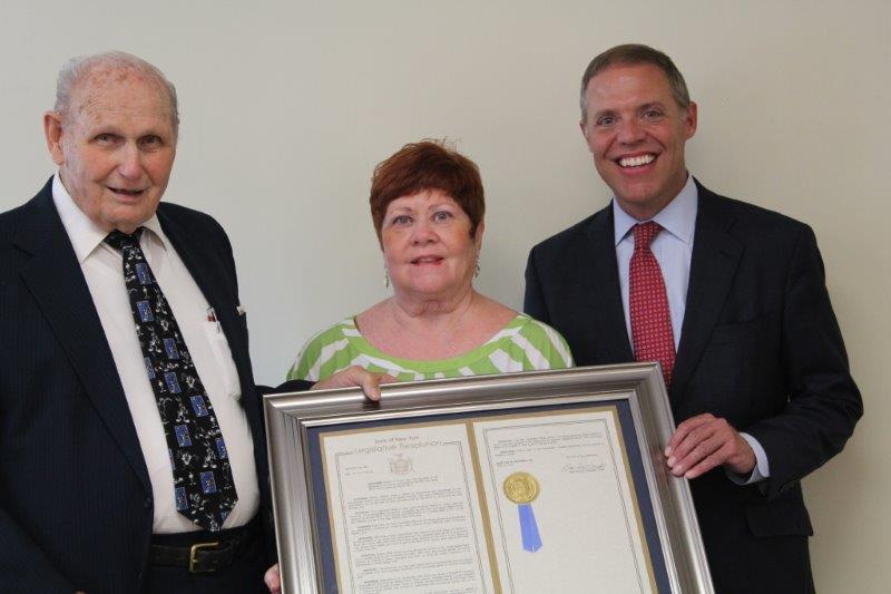 Assemblyman Will Barclay (R,C,I-Pulaski), at right, presents an Assembly Resolution to long-time Fulton volunteer, Mr. Bob Green. Pictured with Barclay are Mr. Green and his wife, Sandy. Mr. Green was honored for his dedicated service to the community.