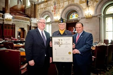 Senator Tom O'Mara (l.) and Assemblyman Phil Palmesano (r.) deliver a copy of the adopted Resolution in the New York State Senate Chamber to Philip J. Swaney, Sr., a distinguished area veteran and Schuyler County resident. Swaney was recognized as the driving force behind the new 'Honor Our Heroes' initiative.