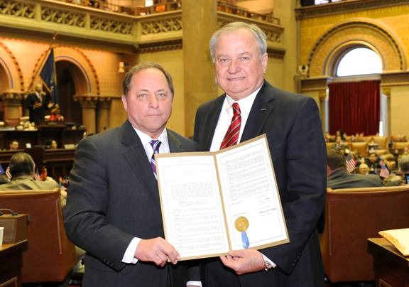 Assemblyman Steve Hawley presents former Assemblyman Charles Nesbitt with the resolution that was passed in honor of Nesbitt's receiving the Distinguished Flying Cross for his heroic rescue of a soldier during the Vietnam War.
