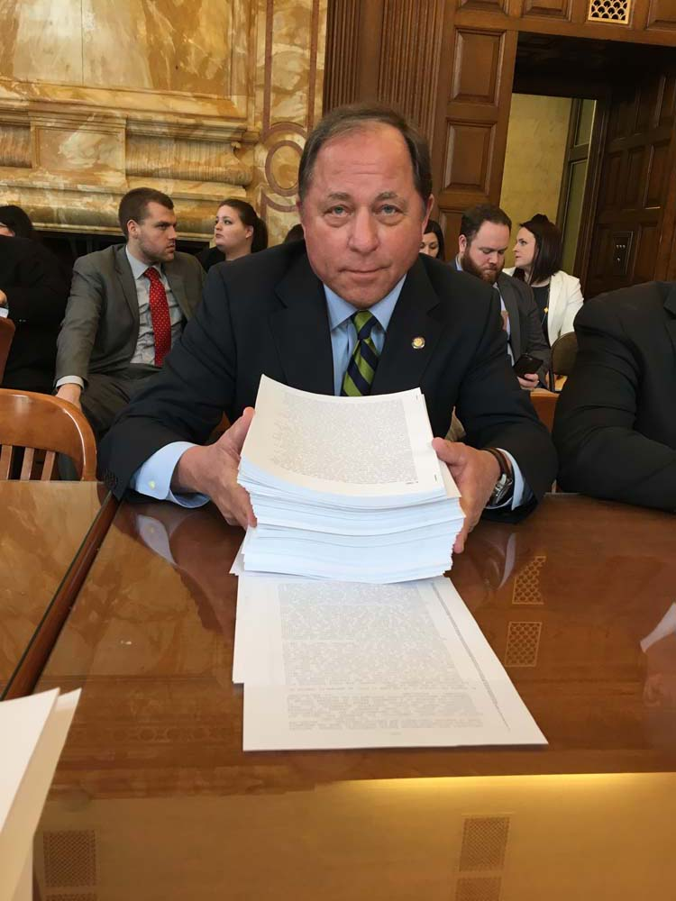 Assemblyman Steve Hawley (R,C,I-Batavia) poses with nearly 2,000 pages of 'budget extender' legislation that was passed by the Legislature Monday following a stalemate in negotiations.