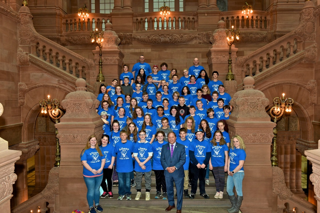 Assemblyman Steve Hawley (R,C,I-Batavia) poses with 70 students from Kendall Schools donning shirts representing the school colors, logo and 'Class of 2024', who visited Albany for a tour of