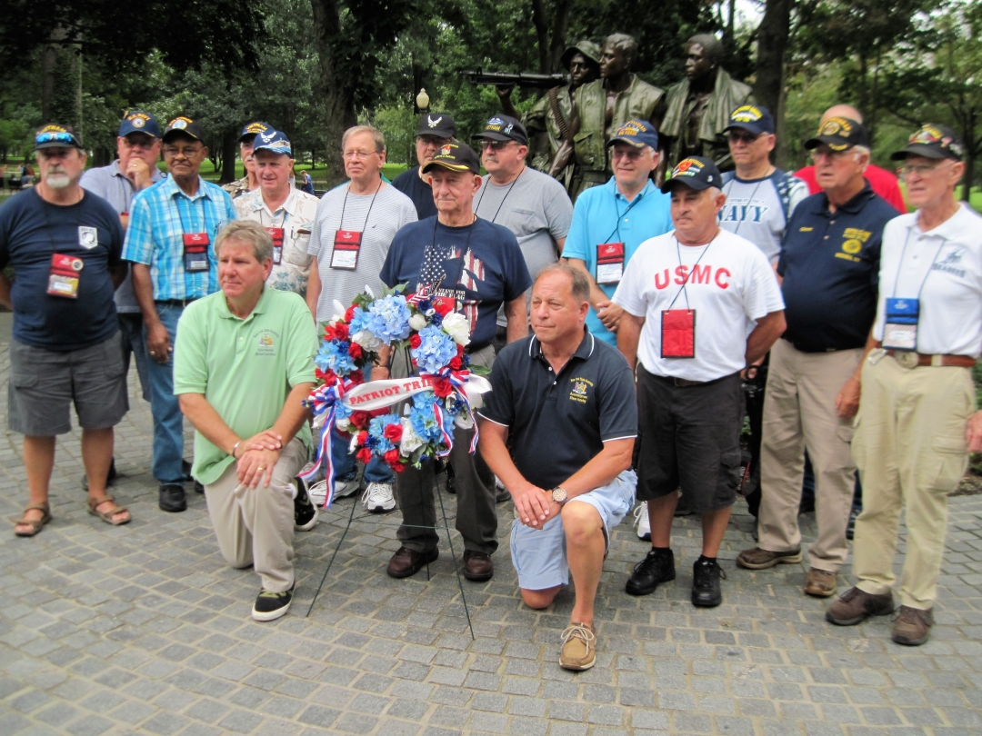 Assemblyman Steve Hawley [right of wreath] poses for a photo with Assemblyman Michael DenDekker [left of wreath] and veterans in front of the Vietnam War Memorial during last year's Patriot Trip