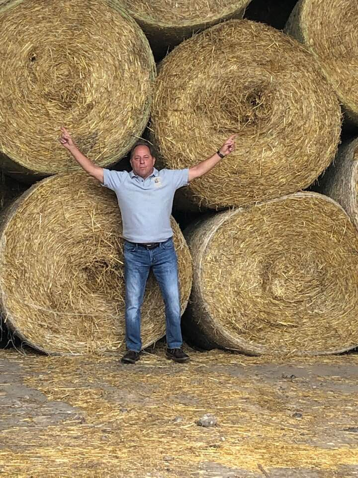 Hawley poses next to giant hay bales at Zuber Farms in Churchville, Monroe Co. where the owners produce corn, hay, wheat and dairy replacements.